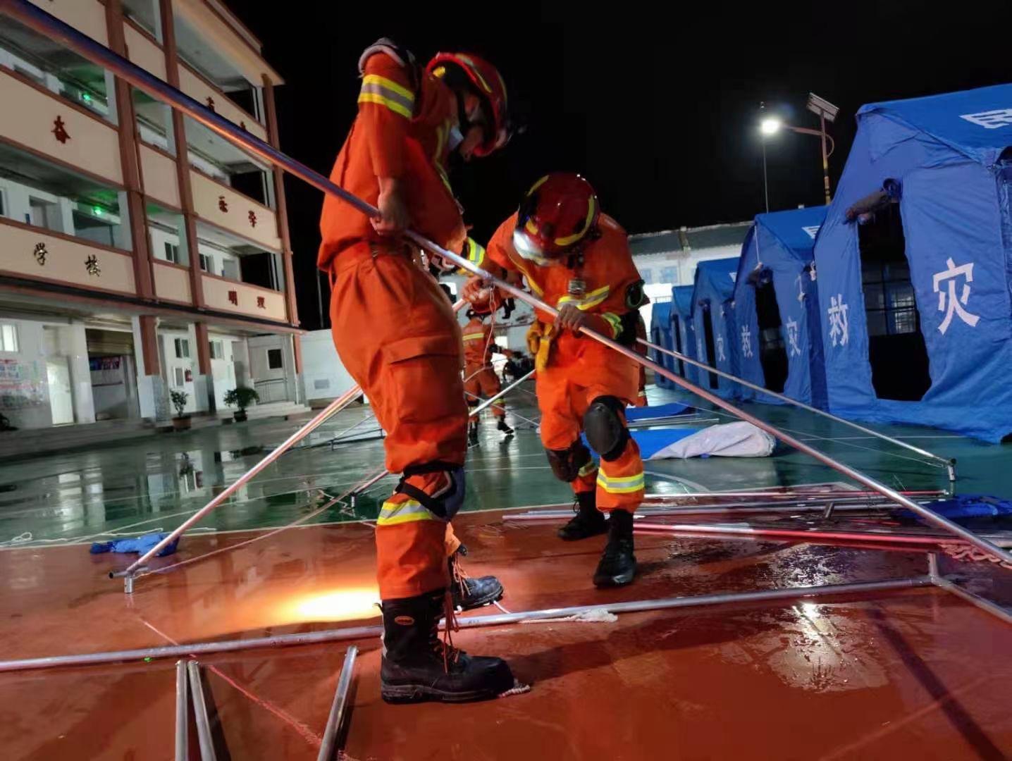 消防人员在双柏县安龙堡中心学校操场上搭建了80顶帐篷。来源:楚雄州消防救援支队