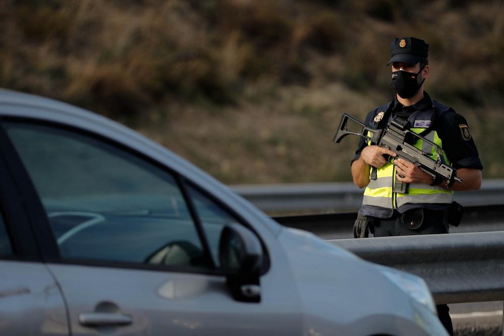 当地时间10月9日,西班牙马德里,为遏制新冠肺炎,警察携枪对过往车辆进行安全及文件检查。当地政府动用7000名警察对被封锁市镇的出入口实施管控。