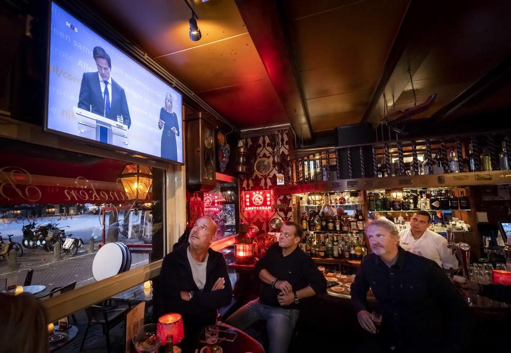当地时间10月13日,荷兰阿姆斯特丹,咖啡店员工在店内观看荷兰首相吕特召开的新闻发布会直播。