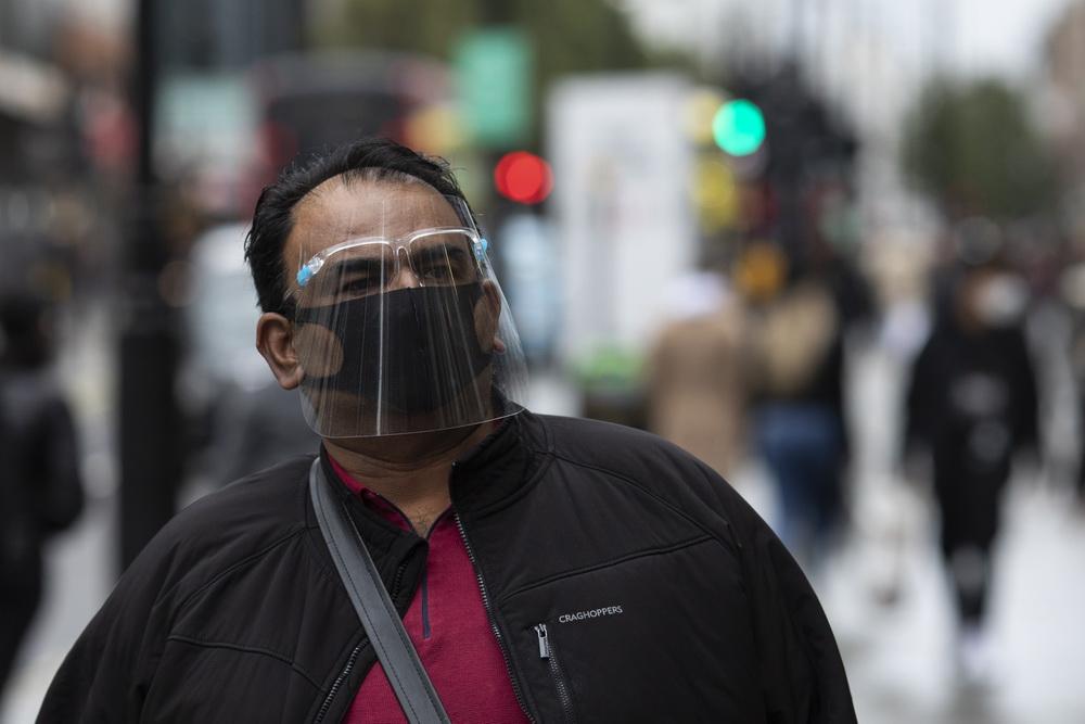 """当地时间10月13日,伦敦市民佩戴防护面具在街头行走。17日起,伦敦将被列入新冠疫情""""高""""等级地区,这也意味着将实施更为严格的封锁措施。"""