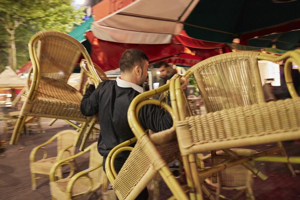 当地时间10月14日,荷兰阿姆斯特丹,餐厅员工把餐椅搬进室内。