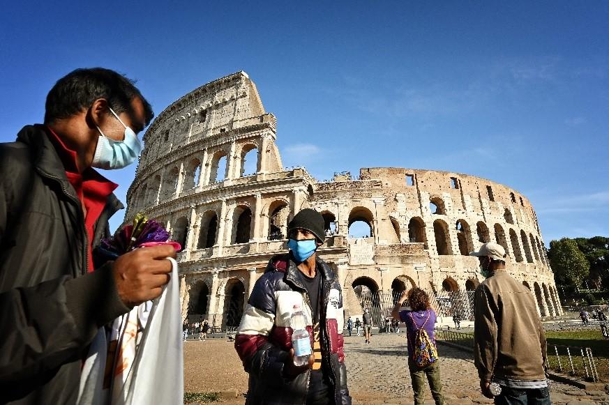 当地时间10月9日,意大利罗马,民众在罗马斗兽场前佩戴口罩。