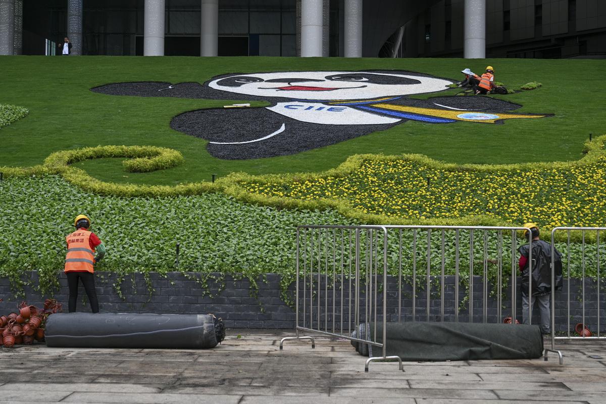 """10月15日,第三届中国国际进口博览会的筹办工作进入最后20天的冲刺阶段。位于上海青浦的国家会展中心(上海)南广场,园林工人正加紧布置进博会吉祥物""""进宝""""等一系列花卉迎宾图案,以最美的绿化景观迎接八方嘉宾的到来。澎湃新闻记者 朱伟辉 图"""