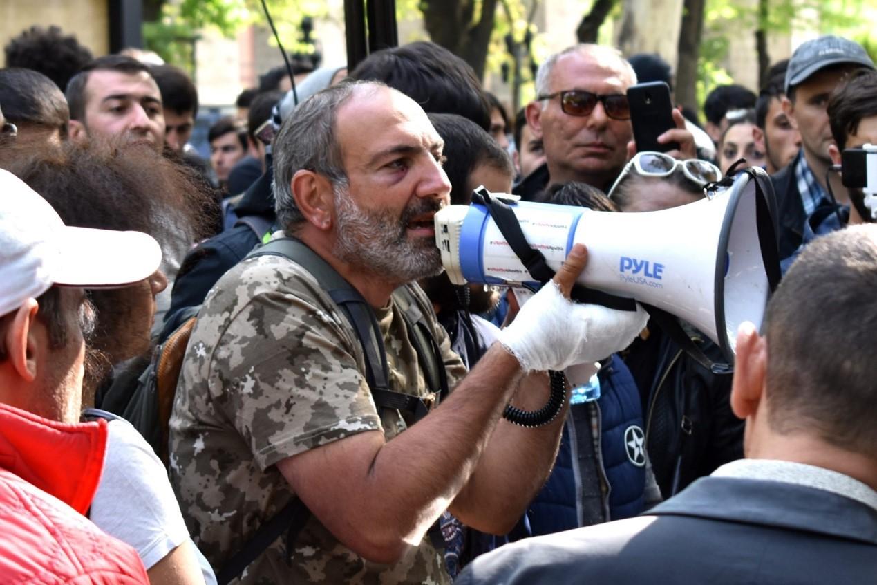 帕希尼杨2018年4月17日在一场反对政府的公共集会上。他手缠绷带,穿着迷彩上衣,模仿梅尔科尼扬的姿态对公众讲话。图源:commons.wikimedia.org