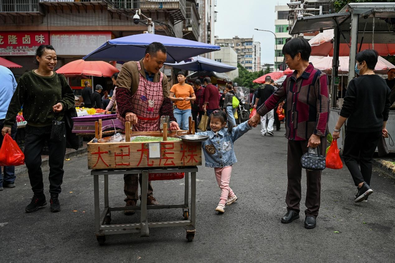 2020年11月23日,三明市广源路菜市场,老人带着孙女在菜市场买菜。
