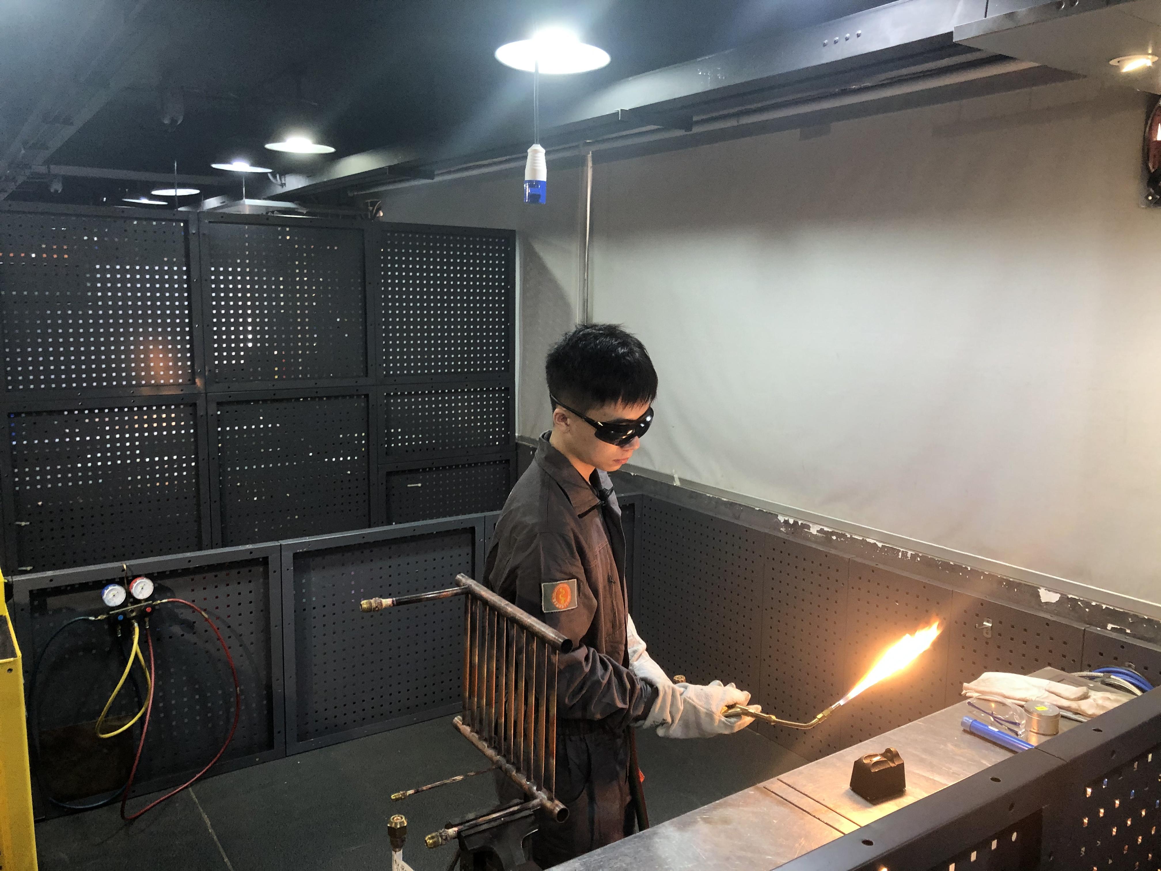 18岁的阮康正在基地进行焊接训练