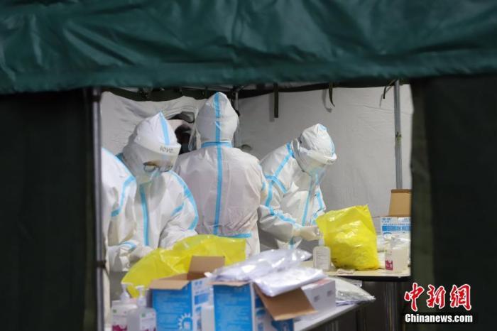 11月21日,受新冠肺炎疫情影响,天津市滨海新区对辖区内全体居民进行大规模核酸检测筛查。图为核酸检测取样现场忙碌的医务工作者。中新社记者 张道正 摄