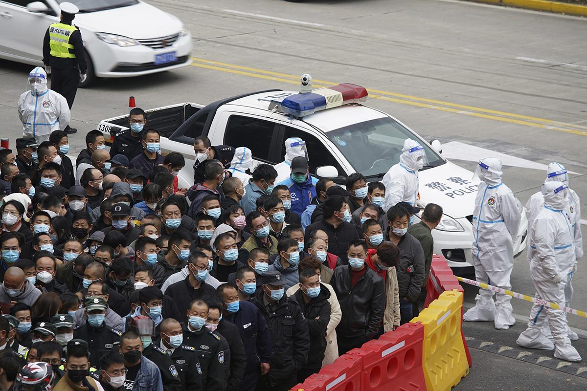 11月23日,上海浦东国际机场,身着防护服的医疗人员准备给排队等候的机场工作人员进行核酸检测。从22日晚起至23日,浦东机场对17719名相关人员开展核酸检测,其中17718人结果阴性,1人结果阳性。澎湃影像 图