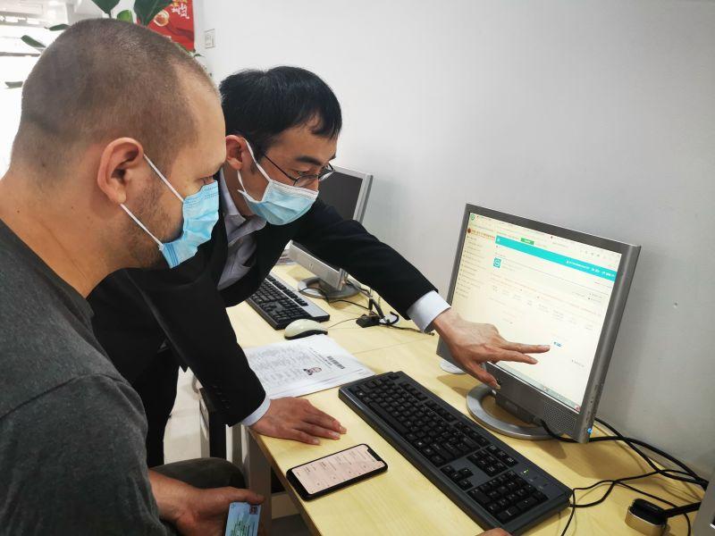 工作人员正在帮助外国专家填写有关资料。宏新 摄