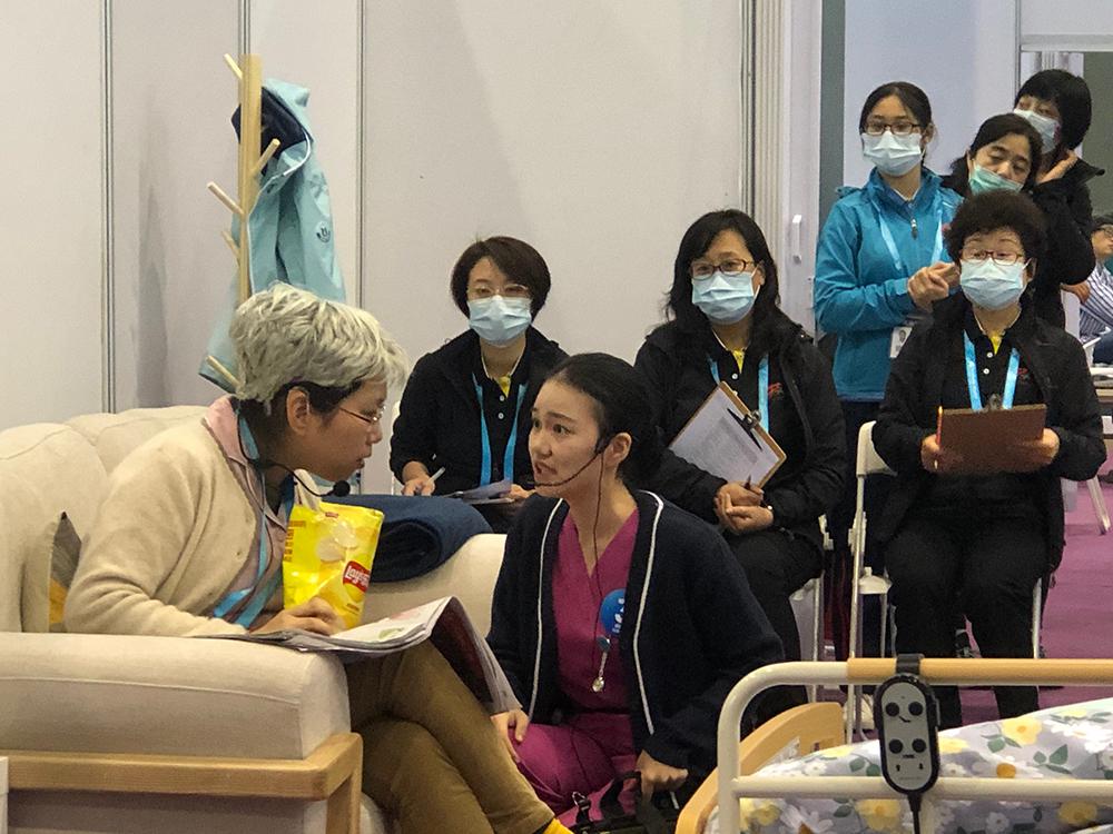 吴怡欣在健康和社会照护比赛项目中与SP(标准化病人)沟通