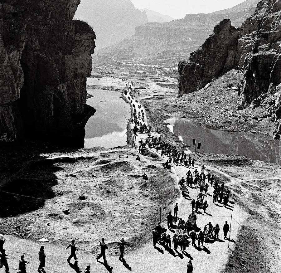 1960年2月,红旗渠工程开始了,数以万计的人们用独轮车把建渠用的水泥、石料源源不断地运往工地。(《移山造海》)