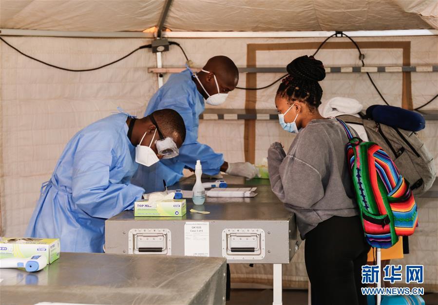 6月3日,防疫工作人员在博茨瓦纳首都哈博罗内的塞雷茨·卡马国际机场登记抵达旅客信息。新华网 图