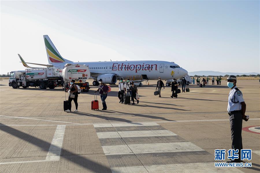 6月3日,在博茨瓦纳首都哈博罗内的塞雷茨·卡马国际机场,乘客佩戴口罩走下飞机。新华网 图