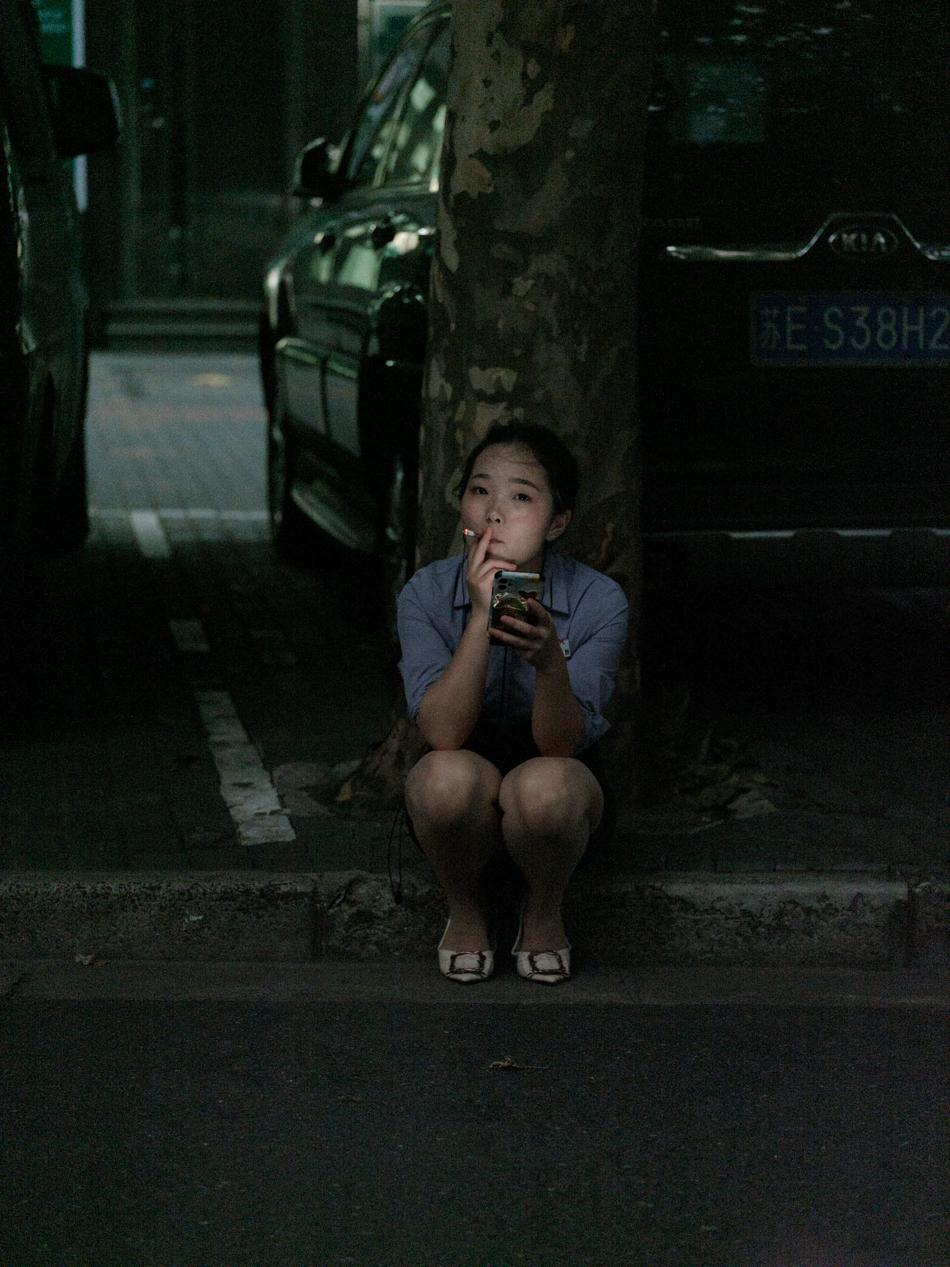 暴雨前,在树下抽烟的女孩,她在苏州河边一家美容美发店工作,上海市黄浦区乌镇路桥南,2020年8月10日。