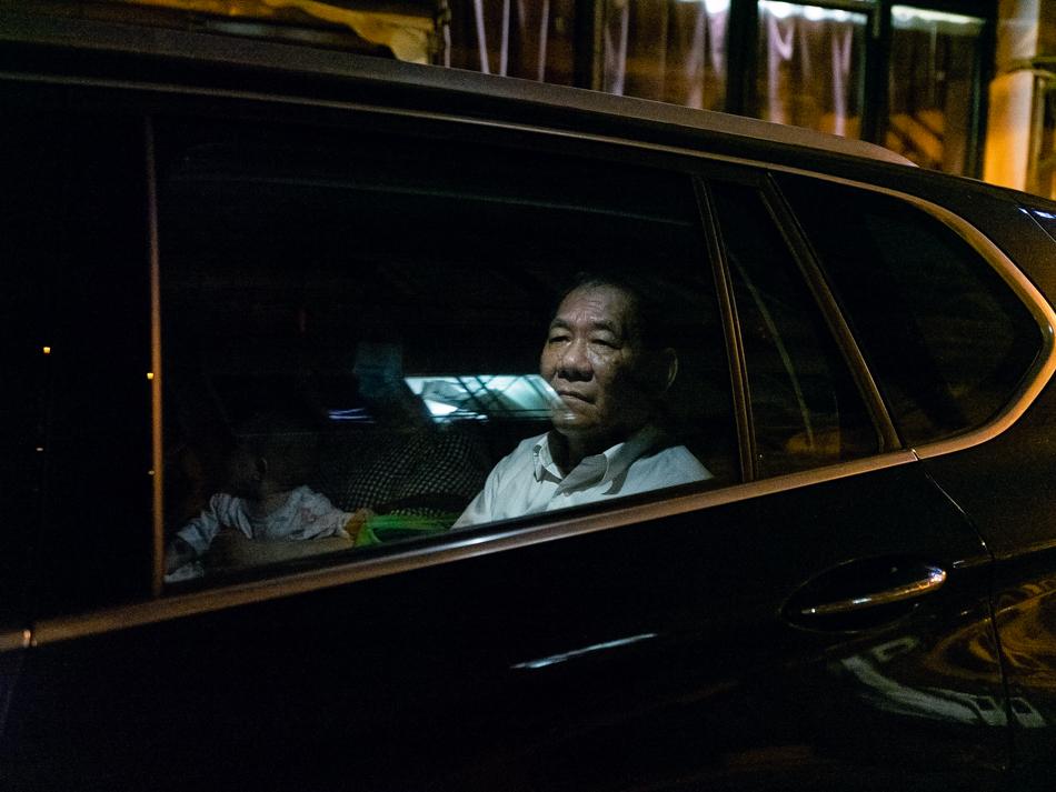 动迁中的西新康里(峨眉路),坐在车中准备离去的动迁户,上海虹口区峨眉路,2020年6月13日。二十年的等待落定尘埃,这是他即将离开的时刻。路灯映射下,面色昏暗,身旁的孙子已进入梦乡。