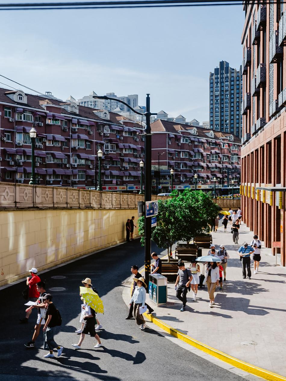 参加城市漫步活动的人群走向西藏路桥的方向,上海静安区西藏北路北苏州路,2020年8月12日。
