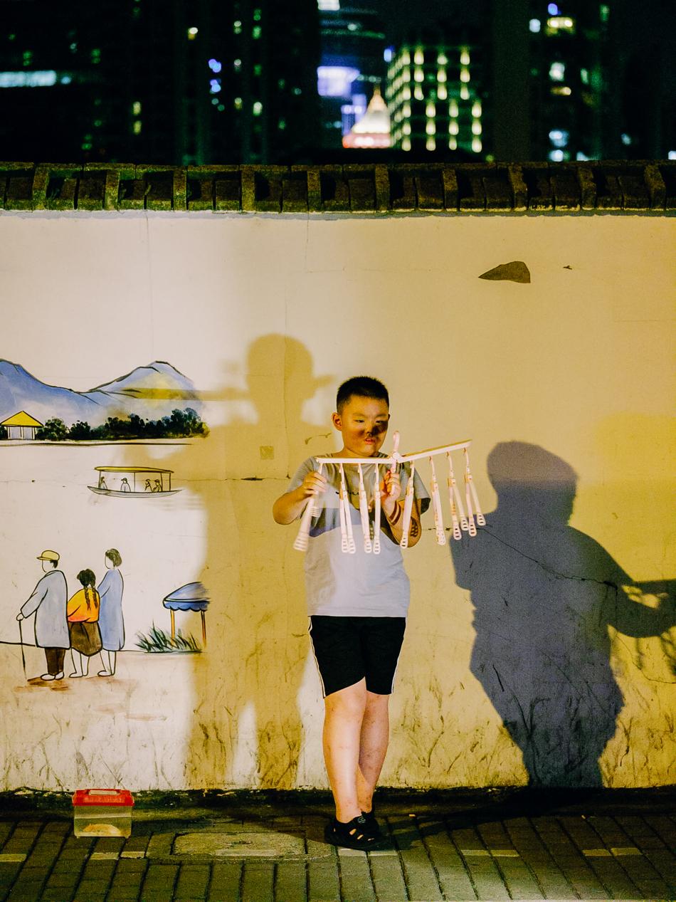 玩晾衣架的男孩,脚边容器装着他的金鱼,上海黄浦区新昌路,2020年8月30日。