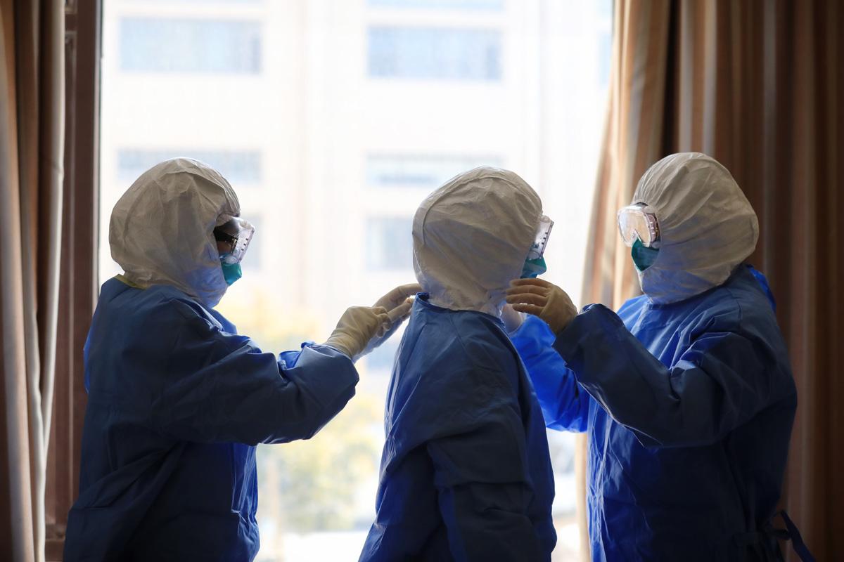 """2020年4月7日,奉贤区,集中隔离点内,由三位90后护士组成的核酸检测采样小组,穿上防护装备,准备投入战""""疫""""排雷。刘华明 图"""