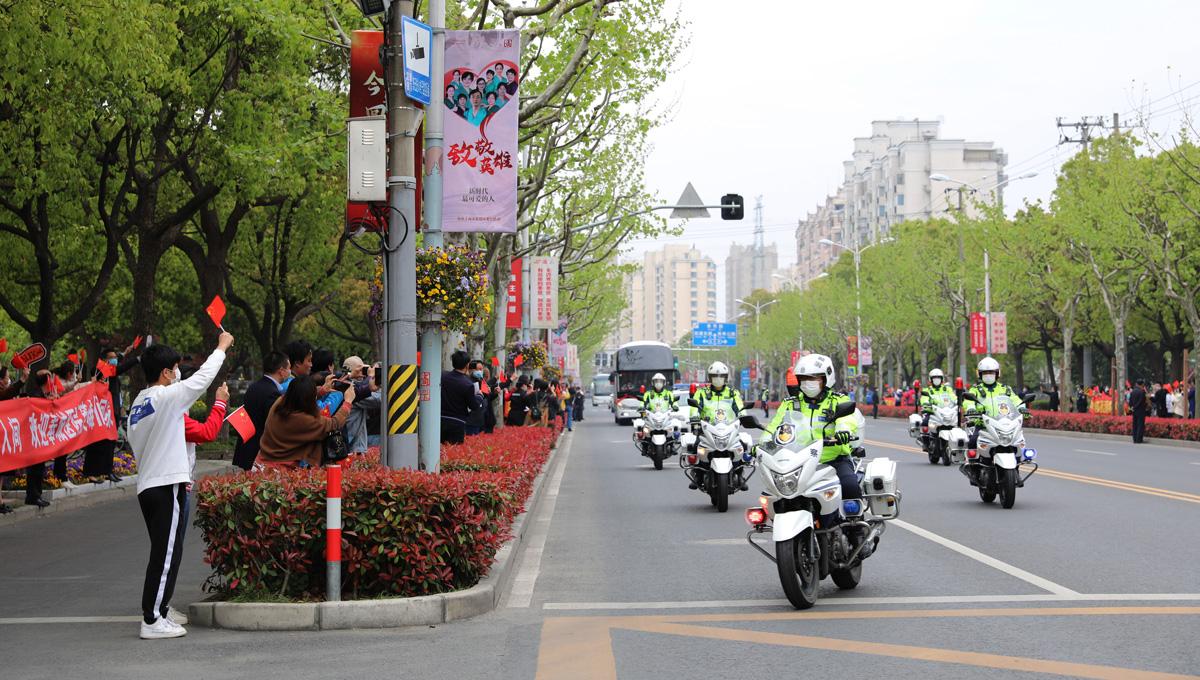 2020年4月14日,奉贤区,警车开道,以最高礼遇迎接英雄归来,路边翘首以盼的奉贤人民夹道迎接援鄂医疗队凯旋。刘华明 图