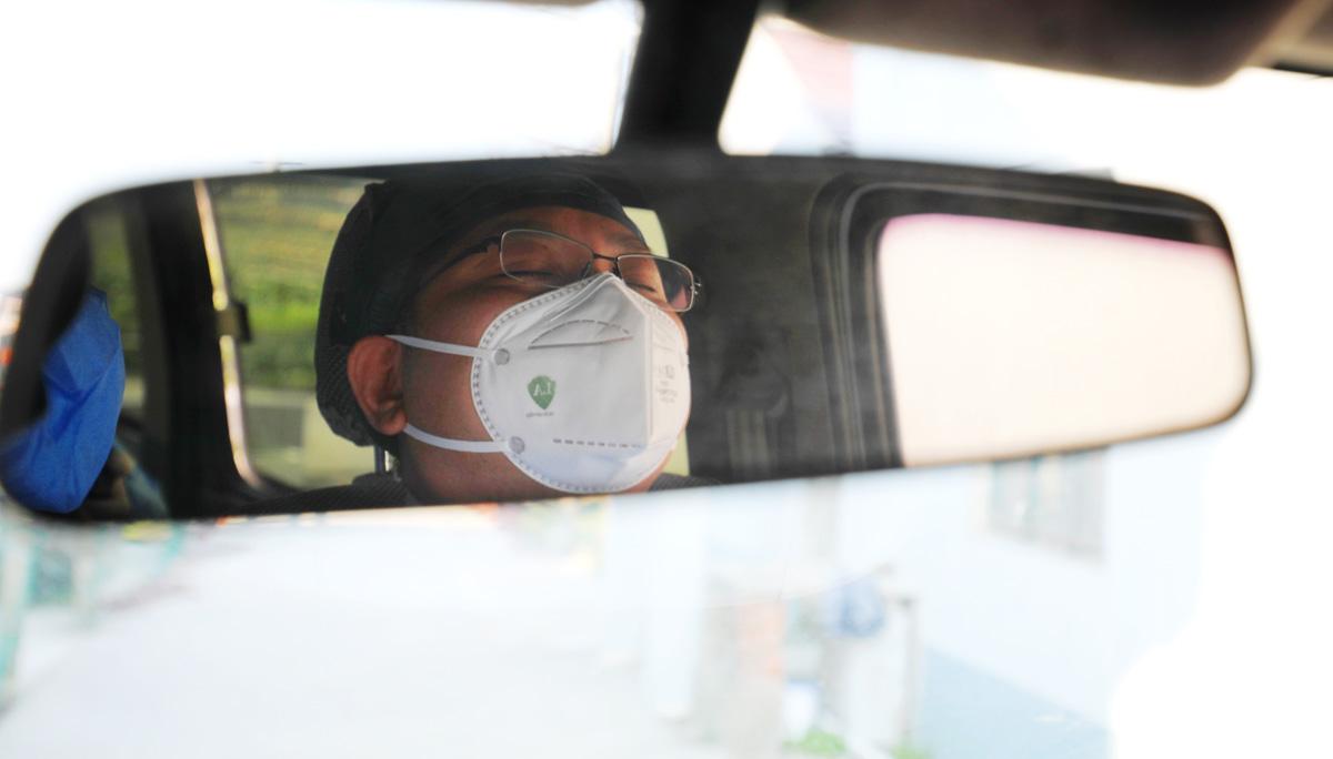 """2020年2月16日,奉贤区,""""嘘,别叫醒他""""(连续一个月没有好好休息的社区医生,结束了半天的居家隔离医学观察后,在返程的车上睡着了,一直到单位了还未醒,随行的同事不忍心叫醒他。)刘华明 图"""