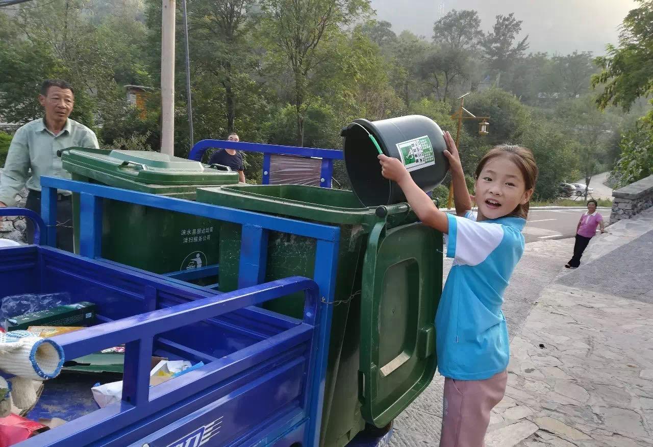 听到喇叭声响,村民出来分类投放垃圾。陈立雯 图