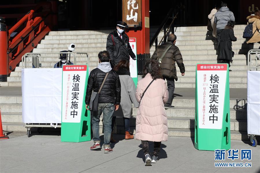 1月9日,日本东京,工作人员指引进入浅草寺的游客测量体温。新华网 图