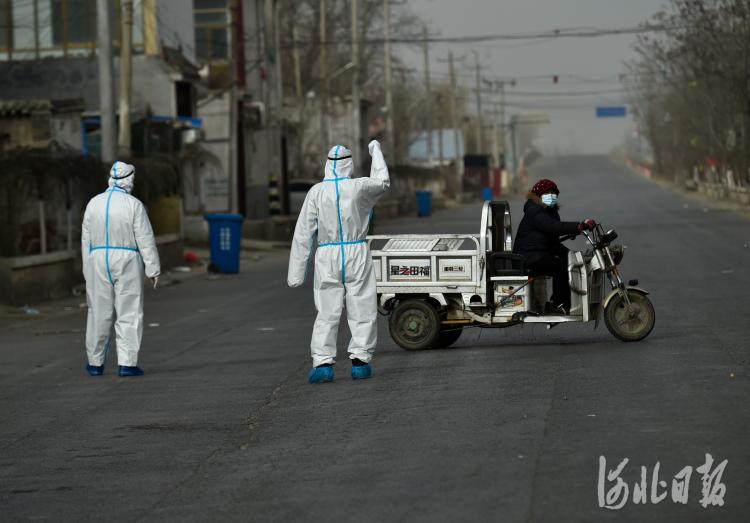 1月13日,在藁城区北桥寨村,疫情防控人员劝返居民。河北日报记者赵杰 摄