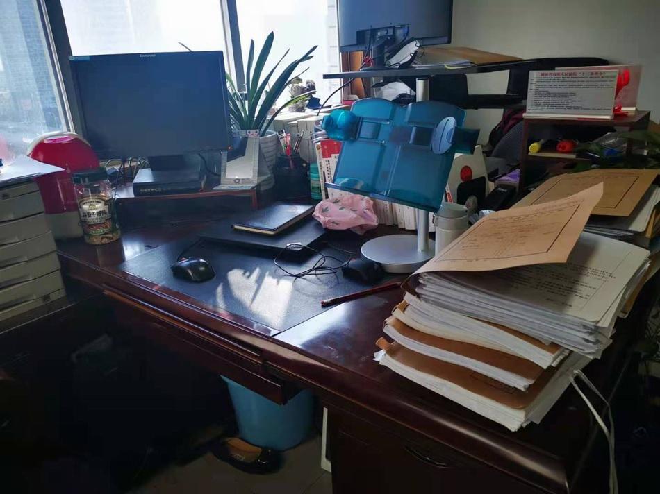 周春梅的办公桌上垒放着待办理的案件。