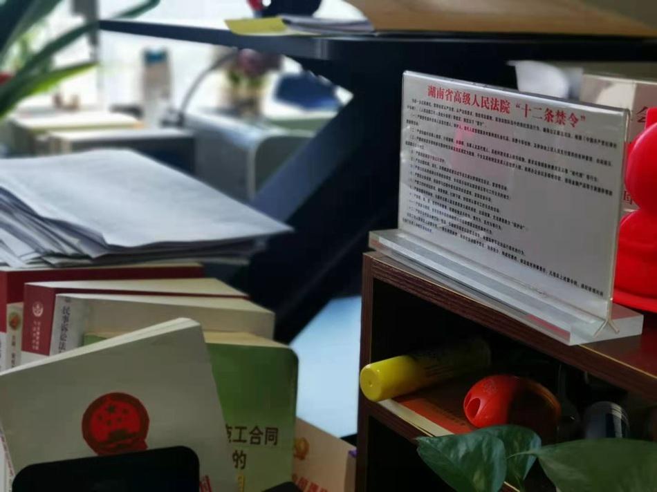 """周春梅的办公桌上立着醒目的《湖南省高级人民法院""""十二条禁令""""》。"""