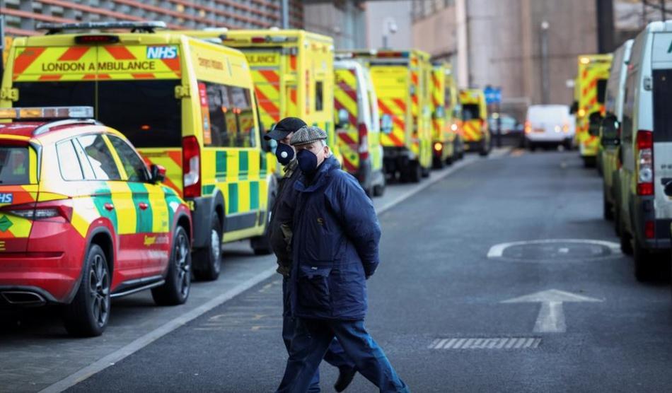 2021年1月12日,英国伦敦,戴着口罩的人走过皇家伦敦医院外的救护车。