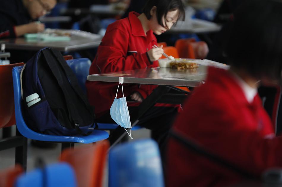 2020年4月23日,石家庄市高三年级复课后,学生们吃饭一人一座,学校在餐桌上准备的口罩挂钩格外温馨。