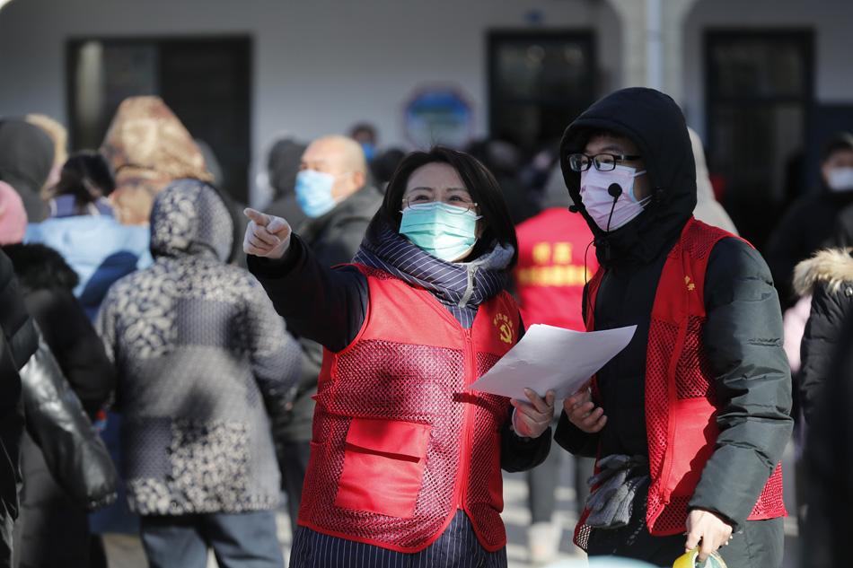 2021年两名穿着棉外套的志愿者在现场沟通协调检测情况,这两天气温一度降至-15℃,社区志愿者们在检测点一待就是十几个小时。