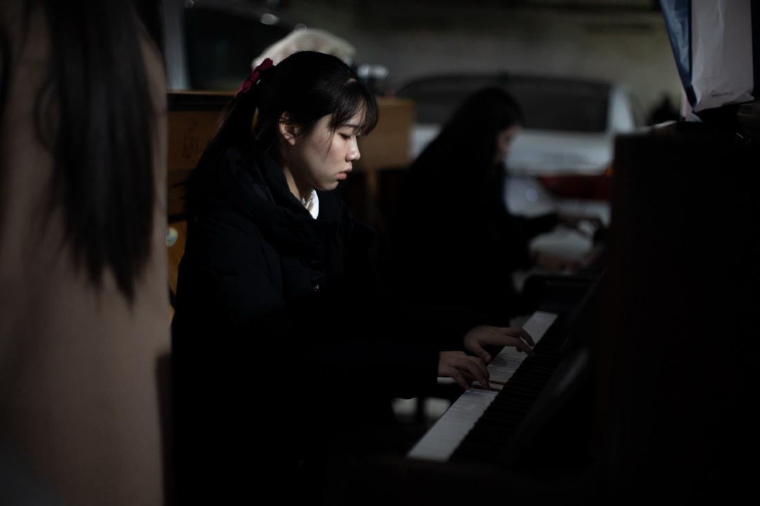 1月16日,成都音乐产业中心的负一层,在两排停车位中间,整齐摆放着十余台钢琴,几位年轻人聚精会神练琴。虽然灯光略显昏暗,但琴声依旧通透,似乎没有受到周遭环境的影响。四川省2021年普通高校招生音乐类专业统一考试正在川音举行,各地考生抓紧时间做最后练习。邹璧宇/视觉中国 图
