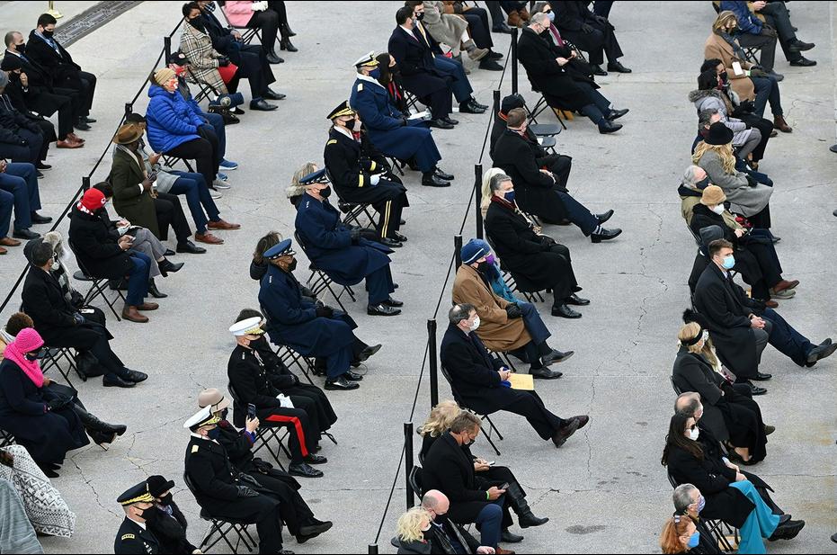 参加典礼的宾客佩戴口罩在国会大厦前就座,彼此之间保持距离。