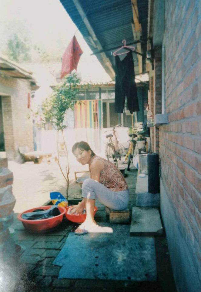 1998年,在一共只有十三平米的北京五环小平房外,母亲在洗衣服。