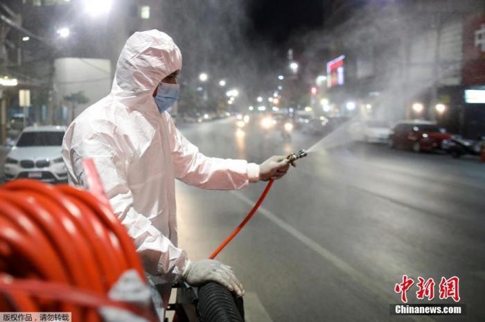 当地时间2021年1月4日,泰国曼谷,一名工作人员上街喷洒消毒剂。 中新网 图