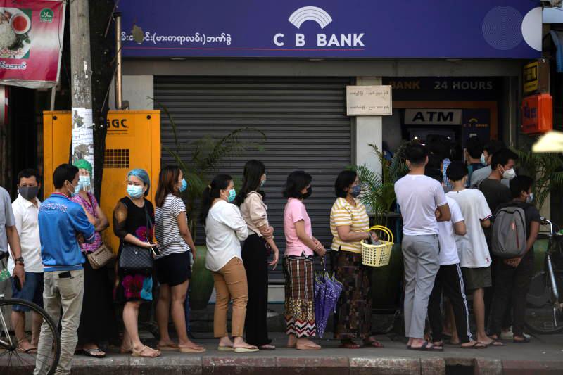2月1日上午,缅甸银行业协会发布通告,宣布缅甸国内各银行全部暂停营业后,缅甸仰光民众排着长队,在银行自动取款机前取钱。
