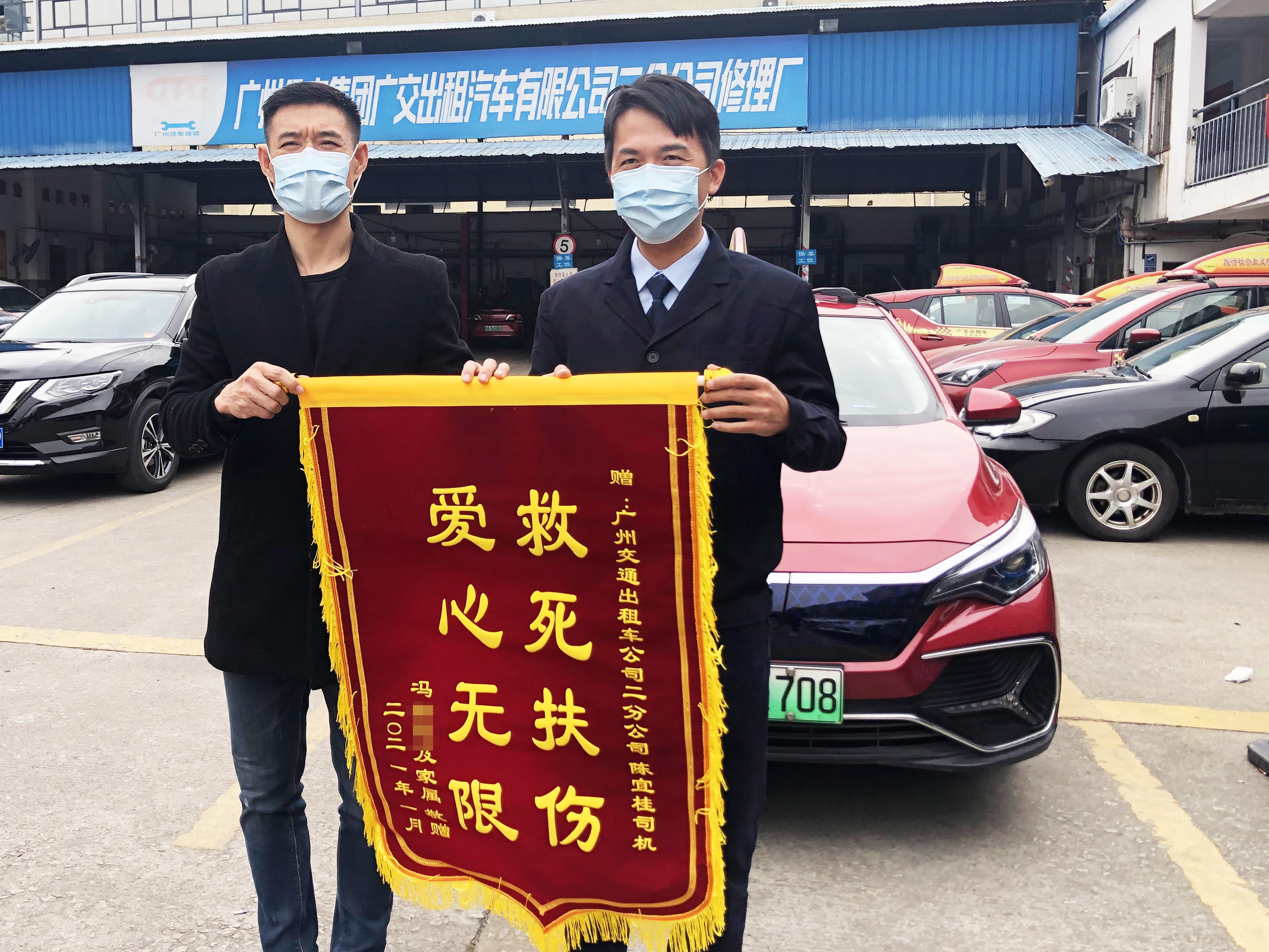 乘客冯先生向的哥陈宜桂(右)赠送锦旗致谢。广州公交集团白云(广交)公司工作人员 供图
