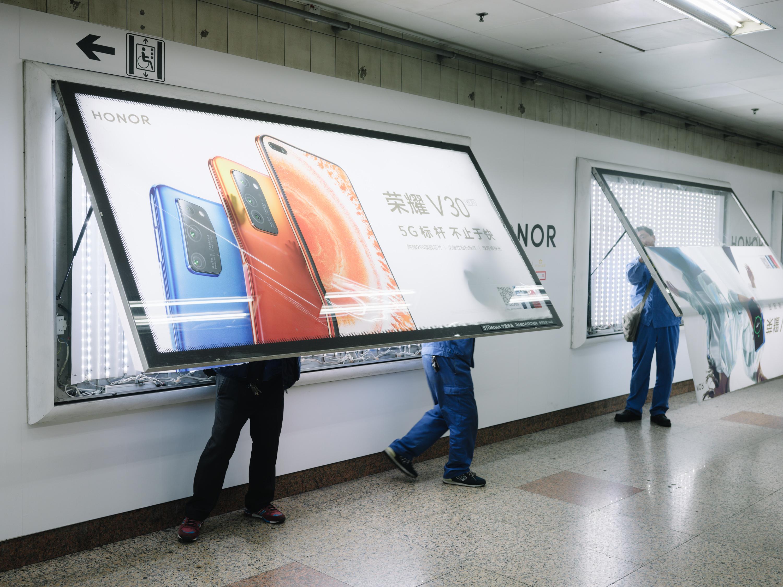 上海地铁站内,工人正把最新的手机广告装上墙。澎湃新闻记者 周平浪 图