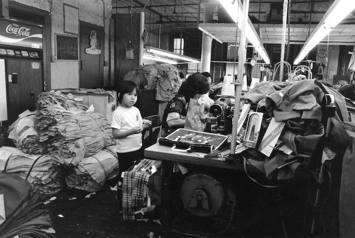 1976年,李扬国在曼哈顿下城伊丽莎白街的一家服装厂拍摄的一位母亲和她的孩子。 CORKY LEE