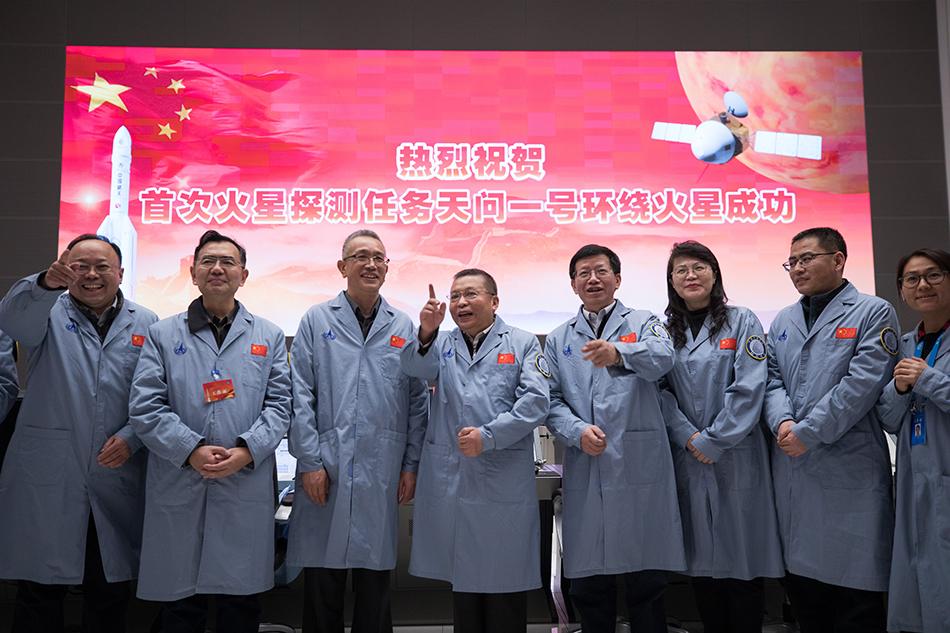 """2月10日,在北京航天飞行控制中心指挥大厅,航天科研人员庆祝我国首次火星探测任务""""天问一号""""环绕火星成功。 新华社记者 金立旺 摄"""