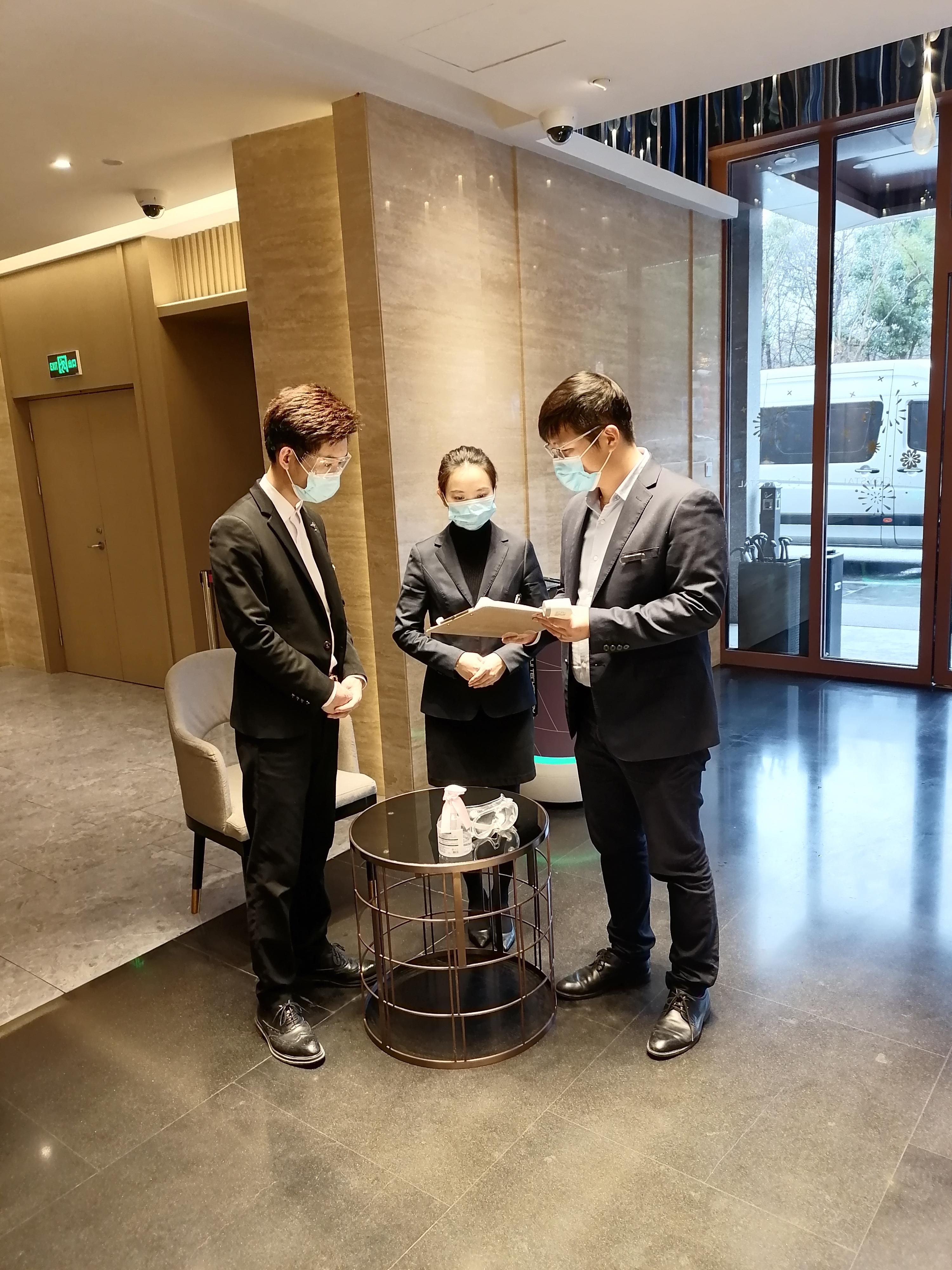 陈烨(右一)在跟酒店员工沟通工作内容。