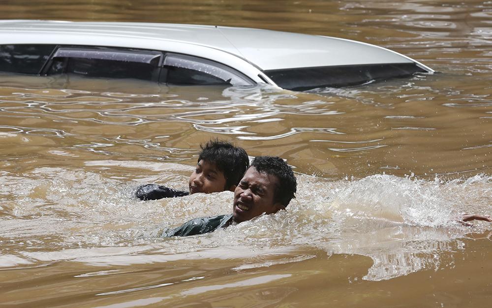 当地时间2021年2月20日,印尼雅加达,当地暴雨引发洪灾,街头遭水淹,民众在洪水中游泳。