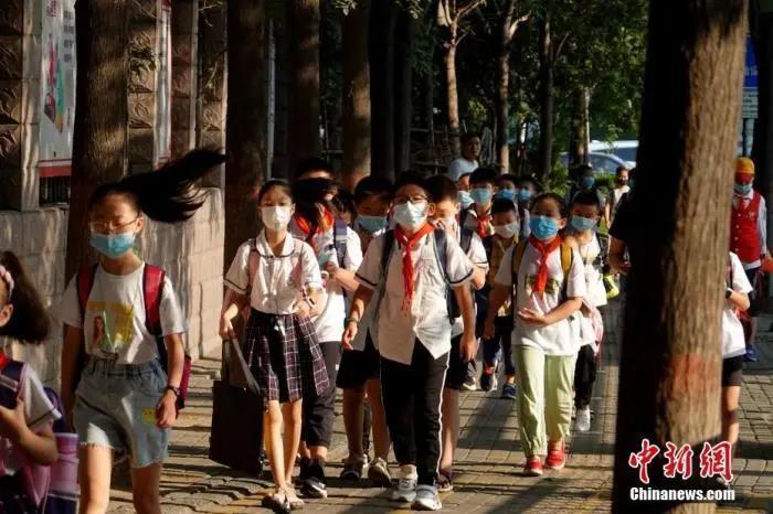 资料图:2020年9月1日,河南郑州,长江东路小学的学生戴口罩有序进入校园。中新社记者 王中举 摄