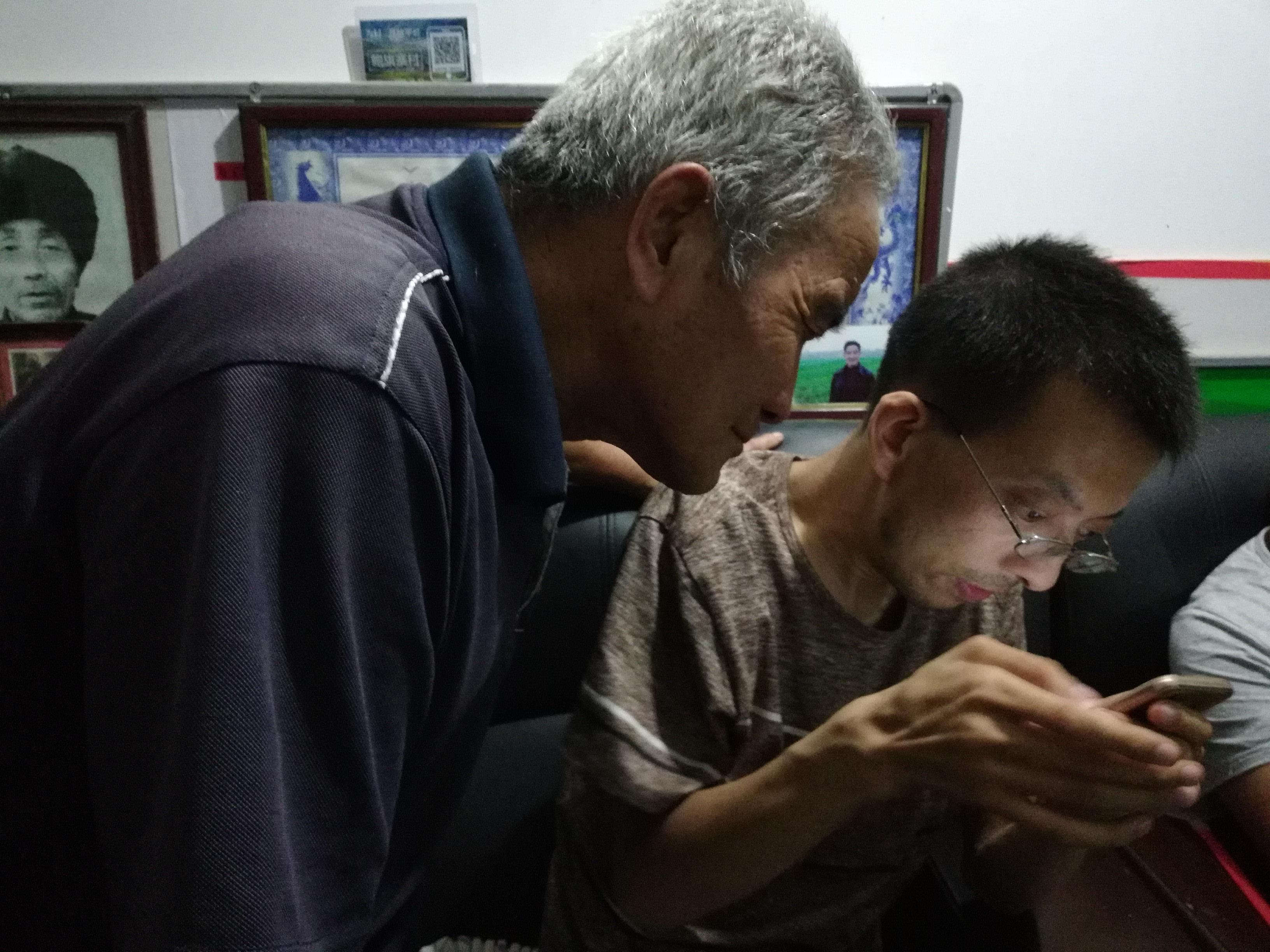 杨锐手把手指导村民如何使用App。