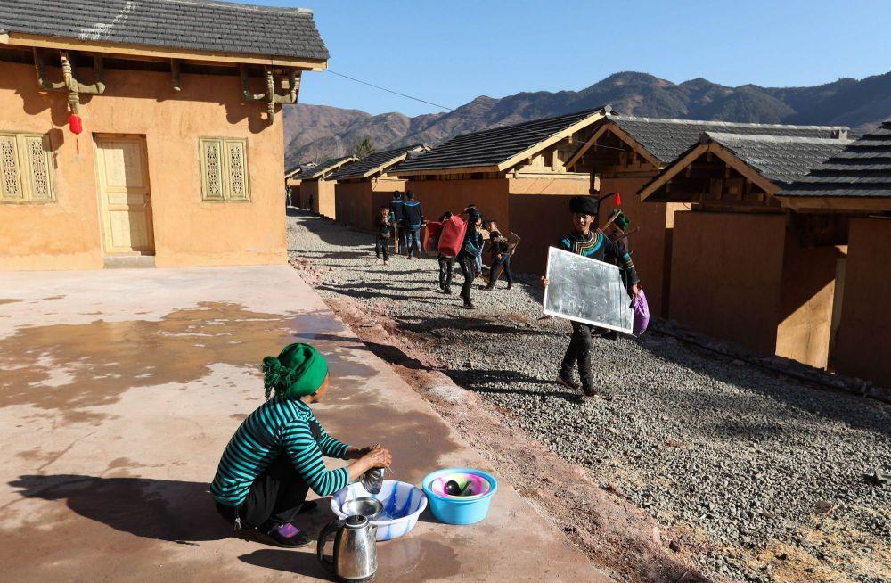 在位于大凉山腹地的四川昭觉县三河村,马海日聪(右一)喜搬新居,这一天,三河村首批29户、168人告别居住多年的土坯房,搬入易地扶贫安置点的新家。2020年,三河村的9个扶贫安置点全部完工,贫困户全都搬进了新房(2019年2月11日摄)。
