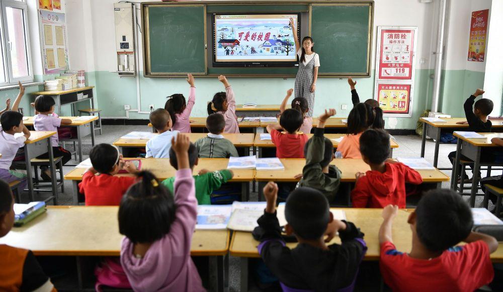宁夏永宁县原隆村原隆小学老师用电子屏给孩子们上课。位于闽宁镇的原隆村,是一个易地移民搬迁形成的新村。在上级支持和福建对口帮扶下,原隆村统筹使用各类资金,做到了家用设施接近城里,公共服务便利完善,政策兜底暖人心窝。如今在原隆村,孩子们走几百米就能到学校,到镇上读高中坐公交车十几分钟就到,村民有个小病小痛在家门口随时能治,医保报销、户籍登记等十几项服务不出村就能享受(2019年9月3日摄)。
