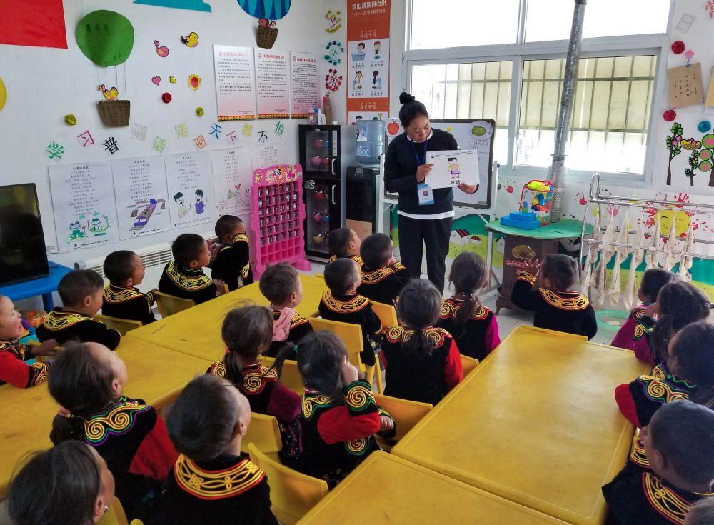 四川昭觉县火普村幼教点老师在给孩子们上课。近几年,教育扶贫让越来越多的火普村村民认识到,只有读书才能斩断穷根,改变命运。以前村民们一见面,比的是谁家子女多,现在比的则是谁家子女学得好。目前,全村137名适龄儿童全部入校读书。村里还建成两个幼教点,确保幼儿学前学会普通话(2019年3月11日摄)。