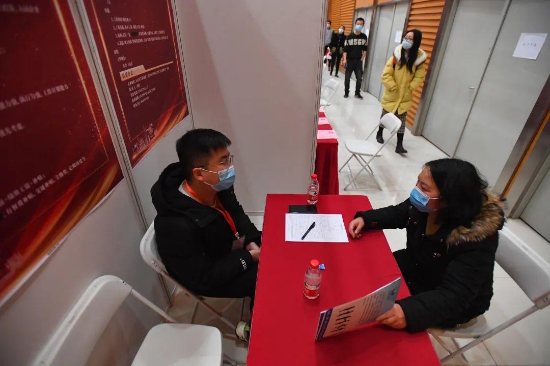 2月18日,在长沙天心文化产业园,求职者(右)与用人单位工作人员现场沟通。记者陈泽国 摄