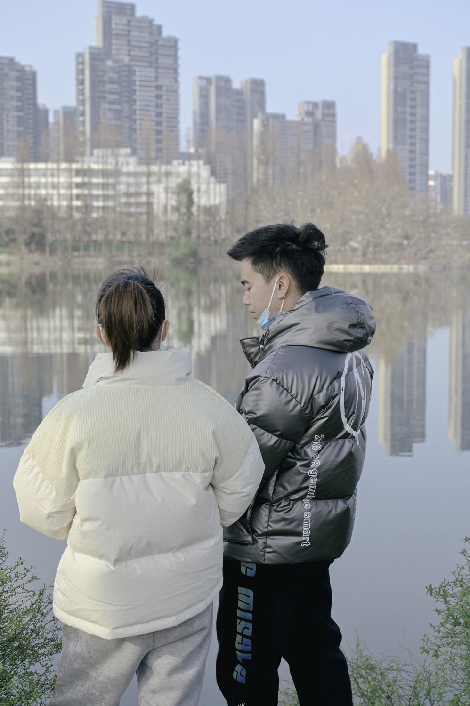 面朝湖的年轻男女。